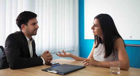 Woman and man sitting at a boardroom table talking