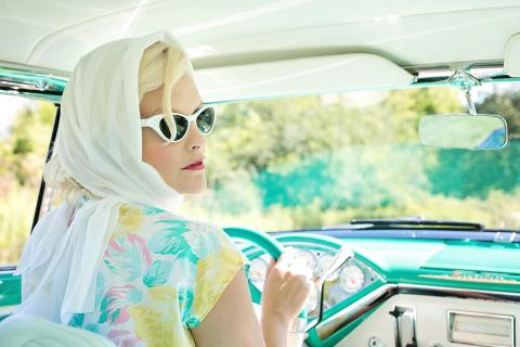 Woman in 1950s style clothing and car