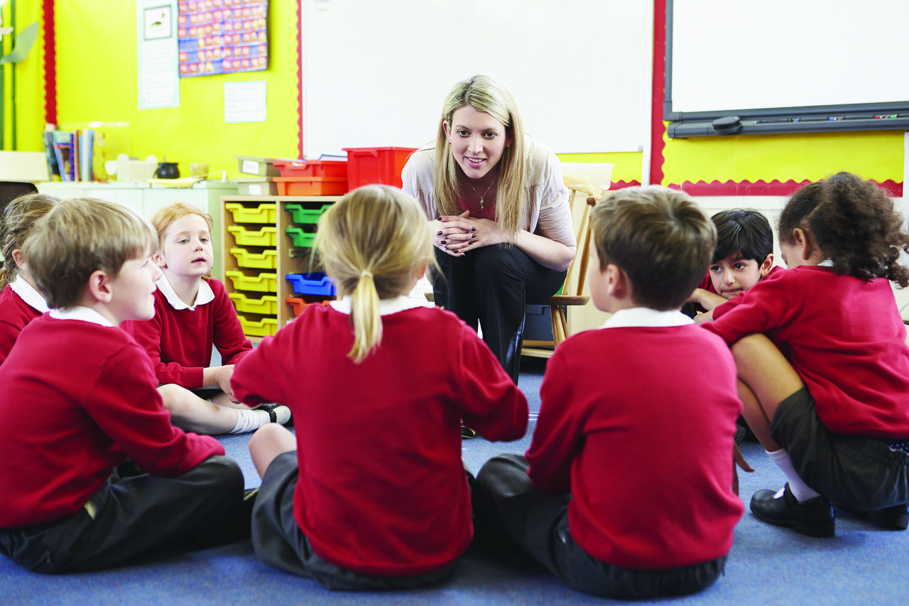Teacher with circle of young students sitting on the floor around her