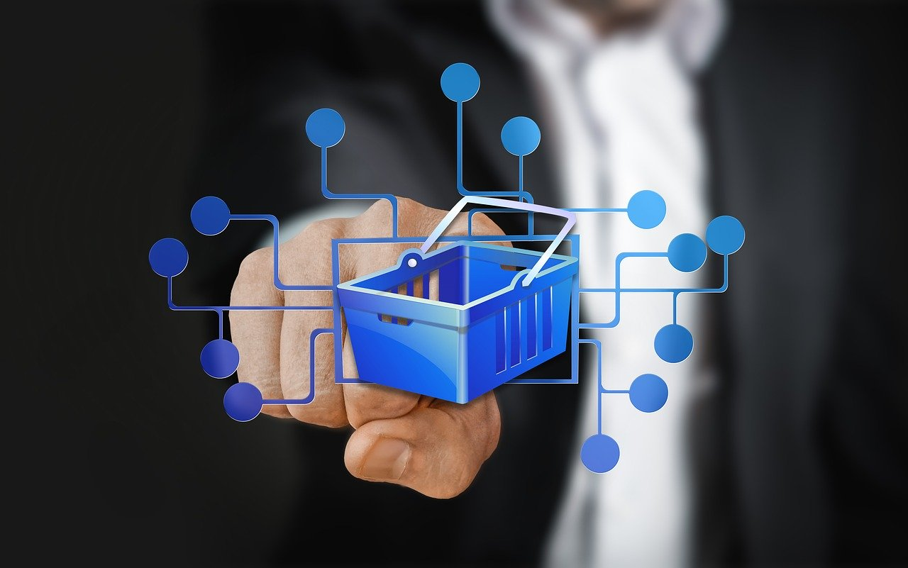 Miniature shopping cart with computer graphic in front of man's fist