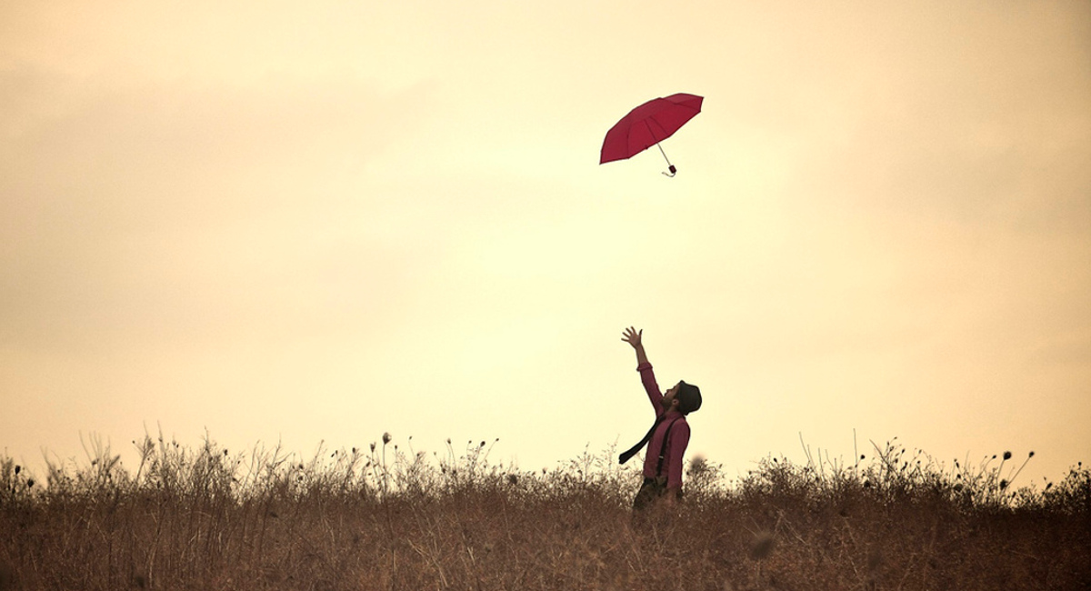 A man throwing a red umbrella in the air