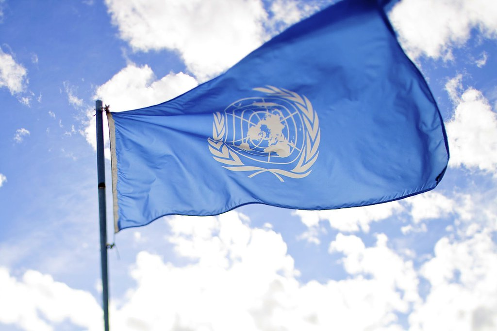 United Nations flag flying with blue sky background