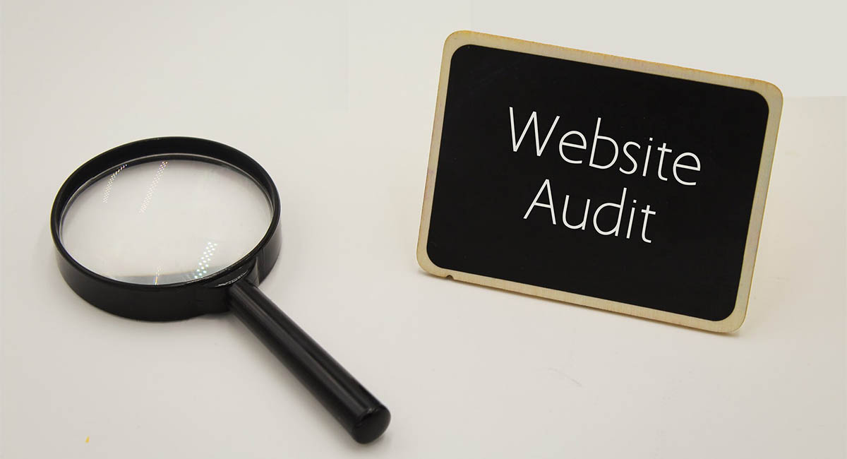 """Magnifying glass, words """"Website Audit"""" on a small blackboard"""