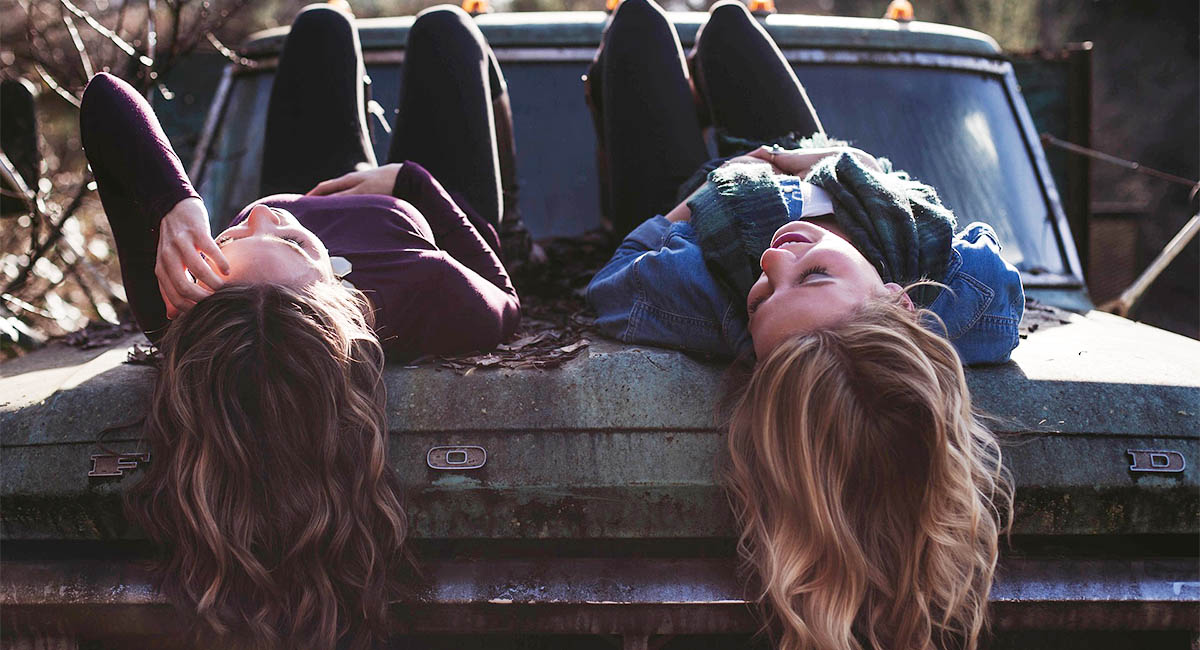 two young women lying on their backs on the hood of an old car with their hair hanging down