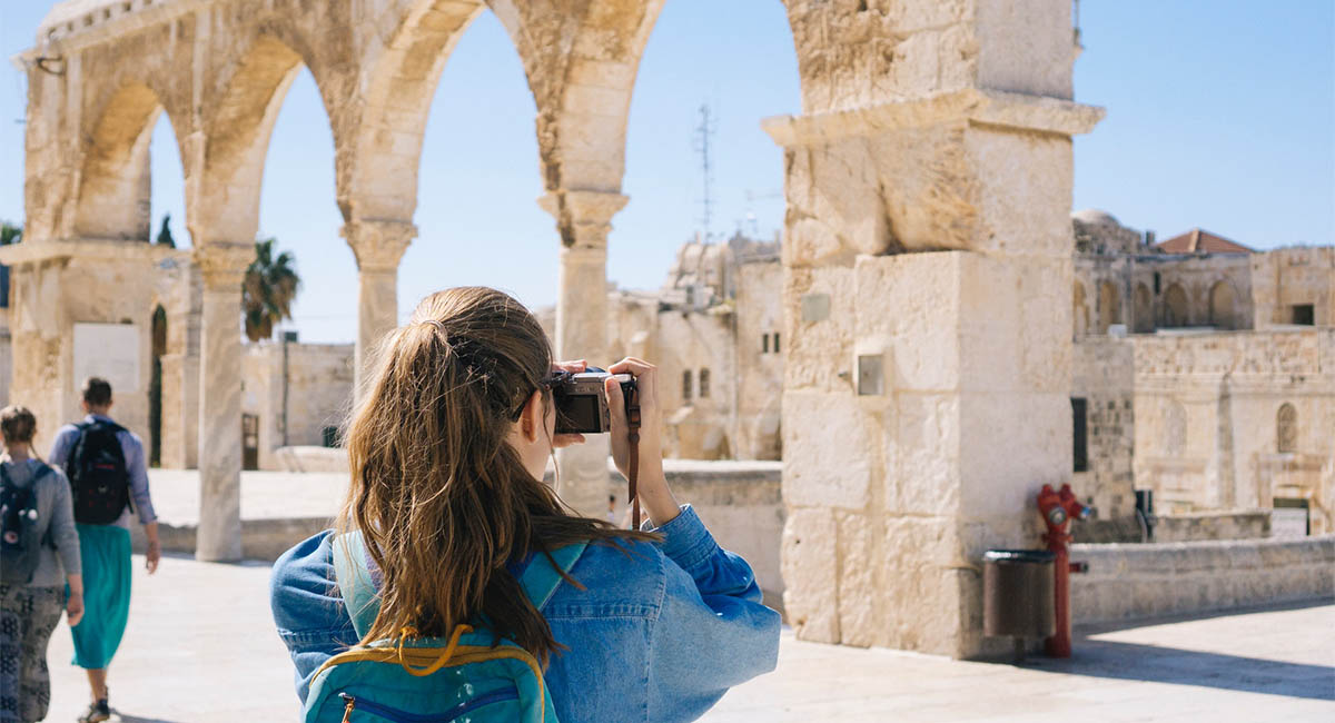 Woman tourist taking a photo of ancient ruins
