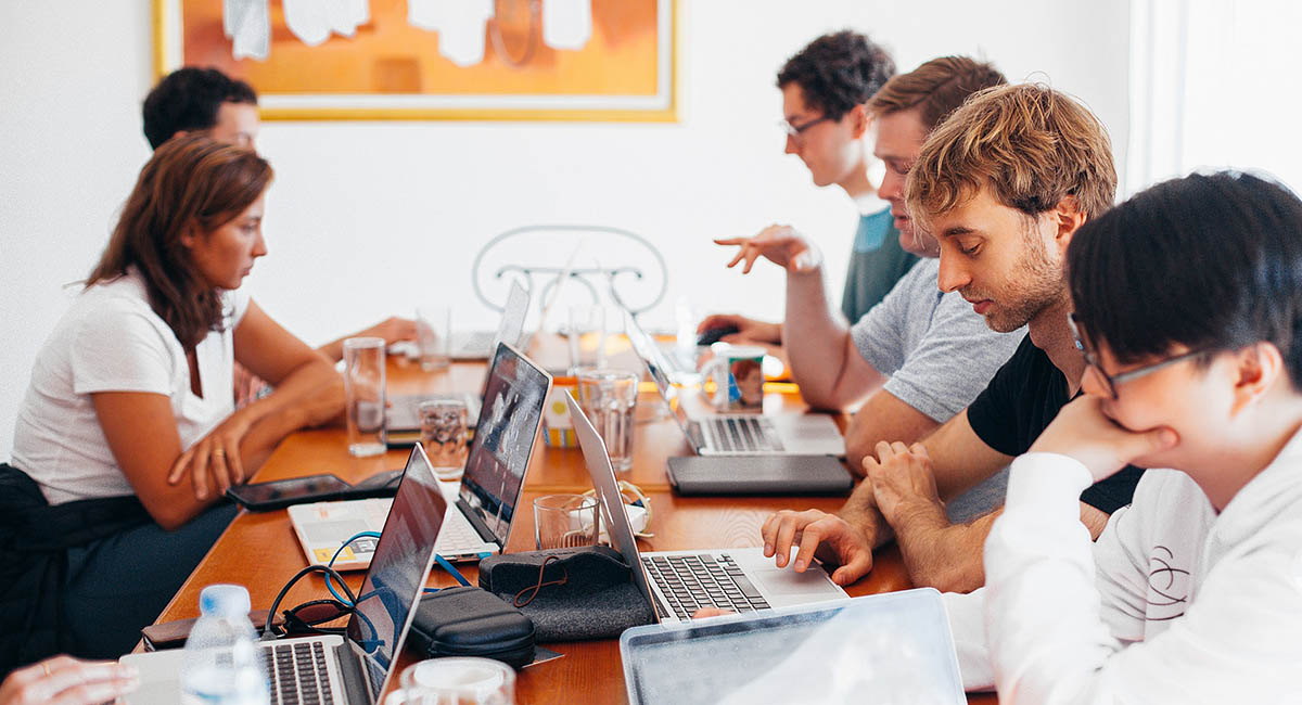 Group of young businesspeople working together at table with computers